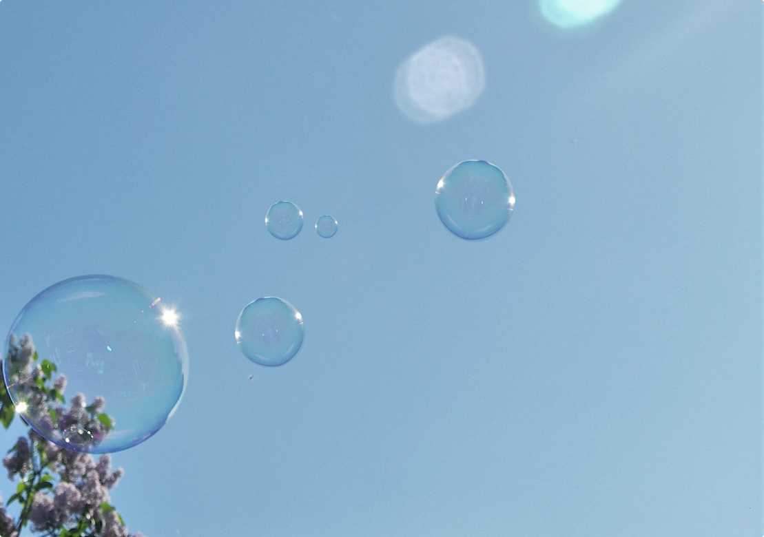 Bubbles floating against a blue sky